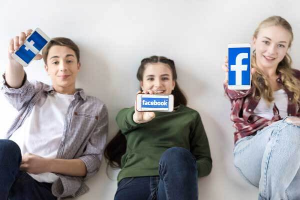 3 teenagers with smartphone wondering how to create a fb stylish name